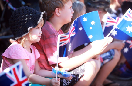 Children in sunshine and holding Australian flgs look outward at a parade