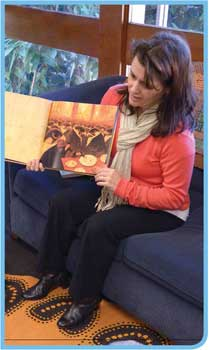 A woman holding a picture book open to display when reading